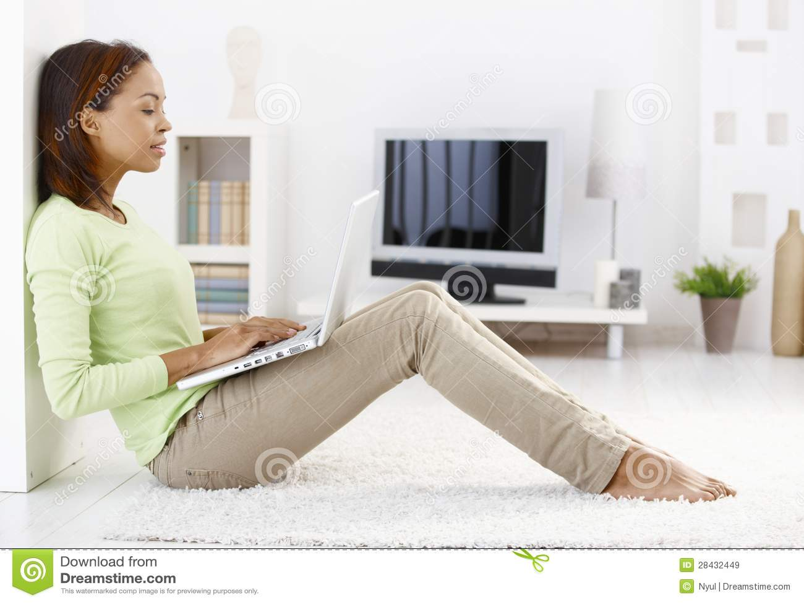 Attractive woman using laptop on floor
