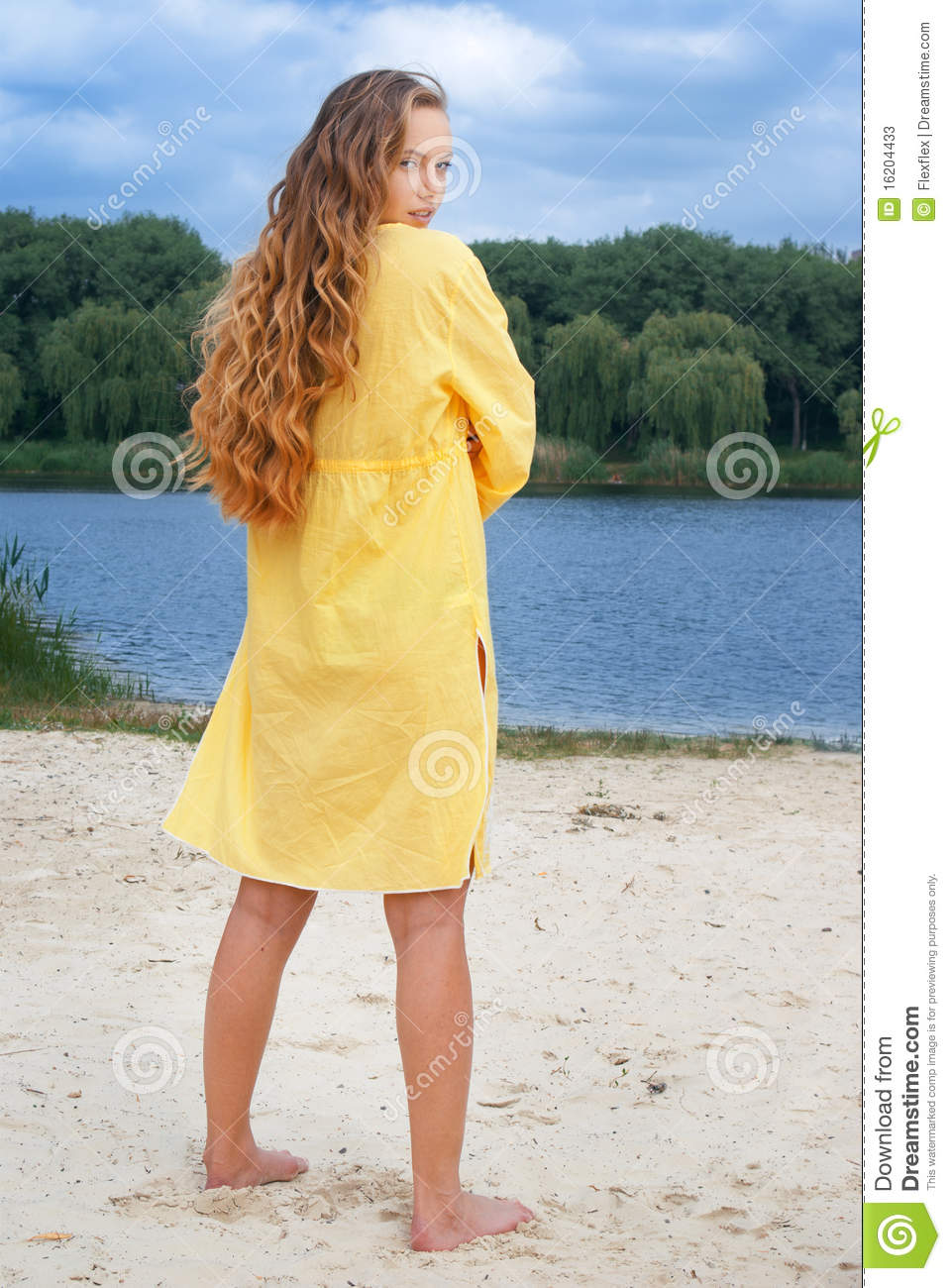 Attractive woman in yellow outfit on river beach
