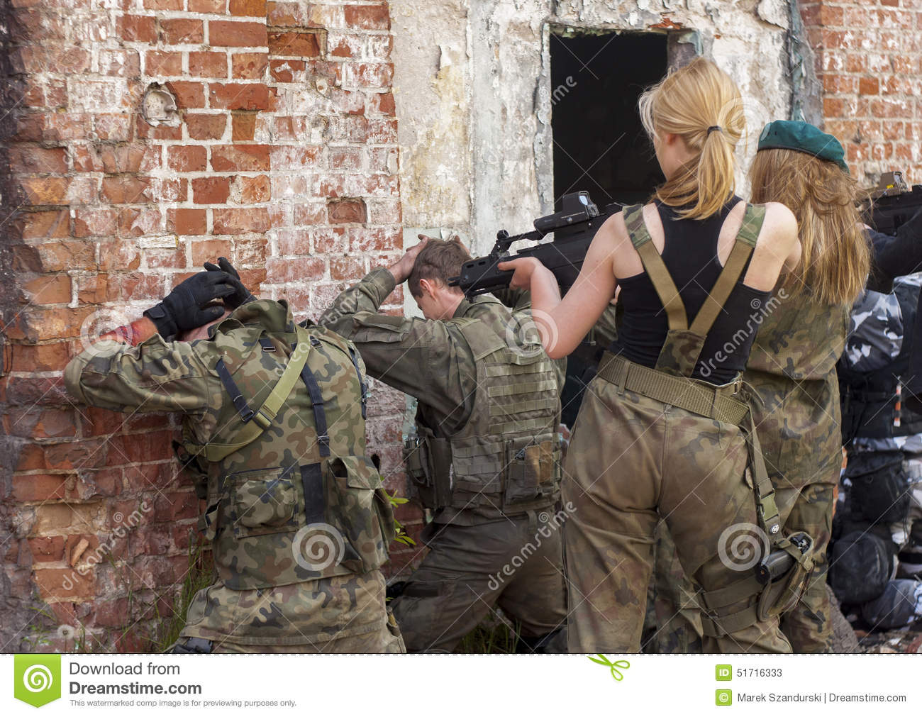 Attractive womens in military uniform, holding gun and aim to sh