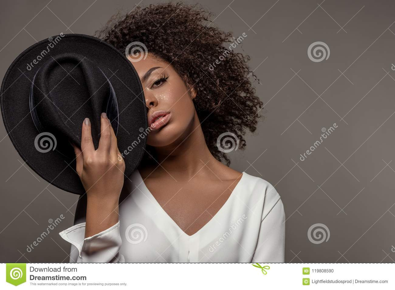 Attractive young african american woman in white shirt holding black hat over half of her face