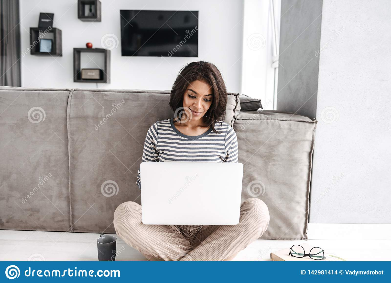 Attractive young afro american woman sitting at a couch
