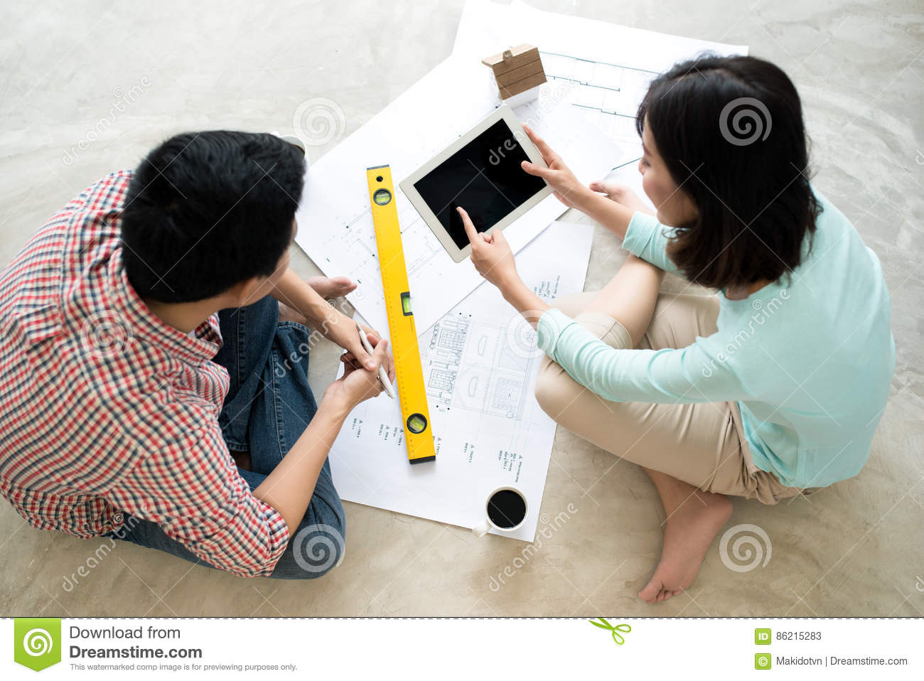Attractive Young Asian Adult Couple Looking At House Plans Stock