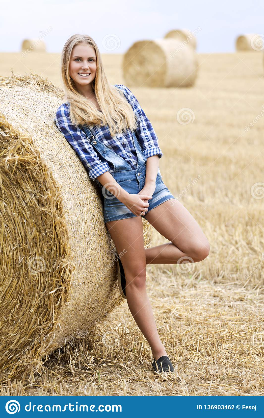 Beautiful Young Blonde Woman Near A Stack Of Straw In A ...