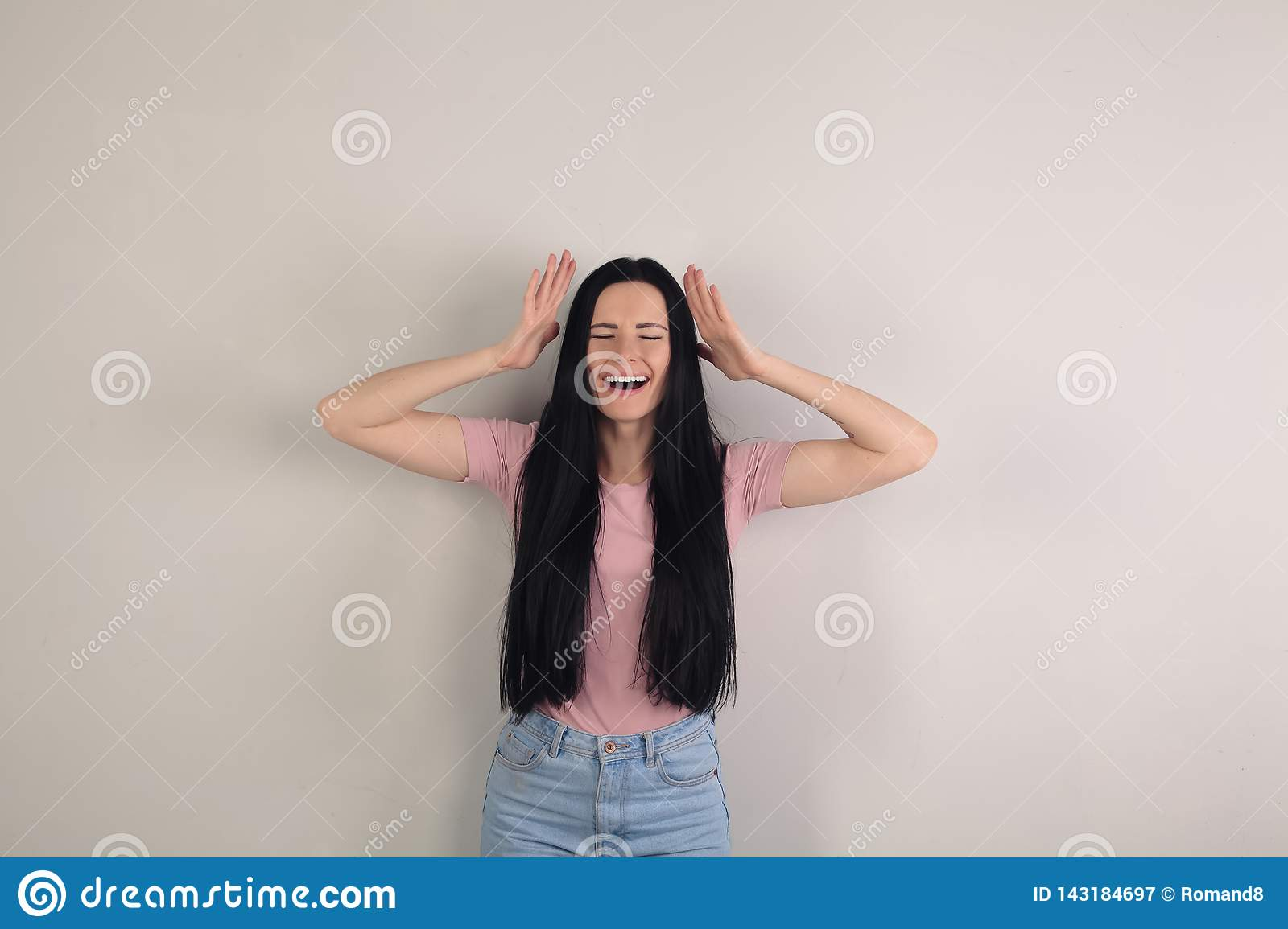 Attractive young brunette woman with long hair is standing by the grey background holding her hands up by the head and screaming.