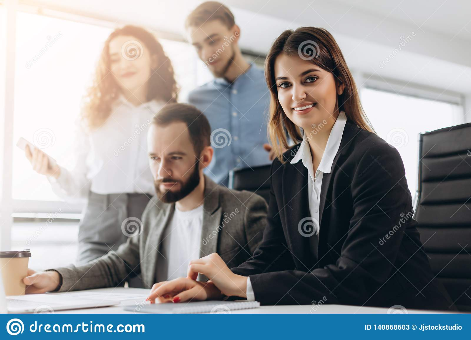 Attractive young business lady is looking at camera and smiling while her colleagues are working in the background