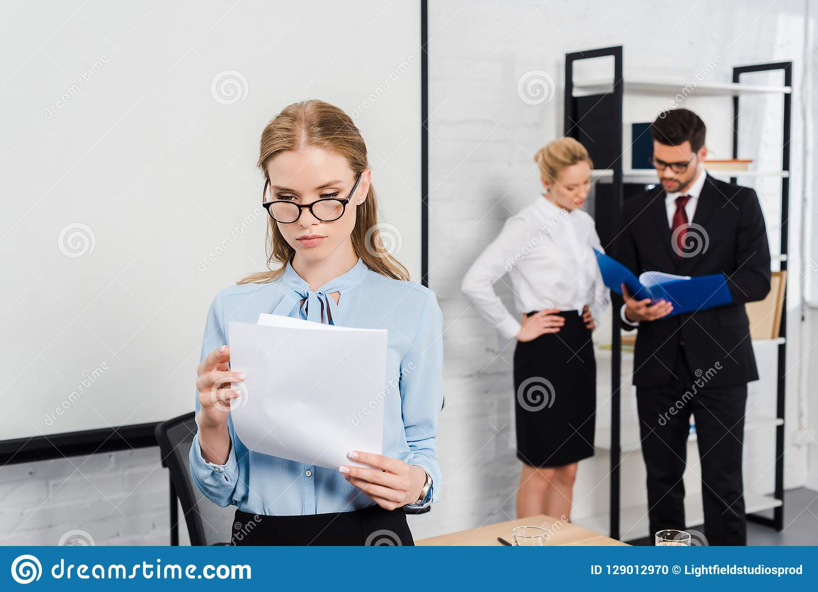 attractive young businesswoman with documents standing at modern office with colleagues