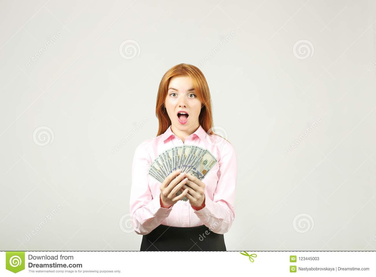 Attractive young businesswoman posing with bunch of USD cash in hands showing positive emotions and happy facial expression.