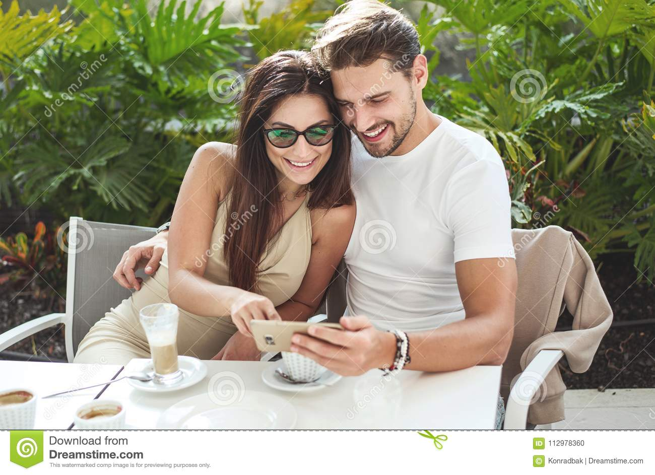 Attractive couple in the cafe, uisng smartphone