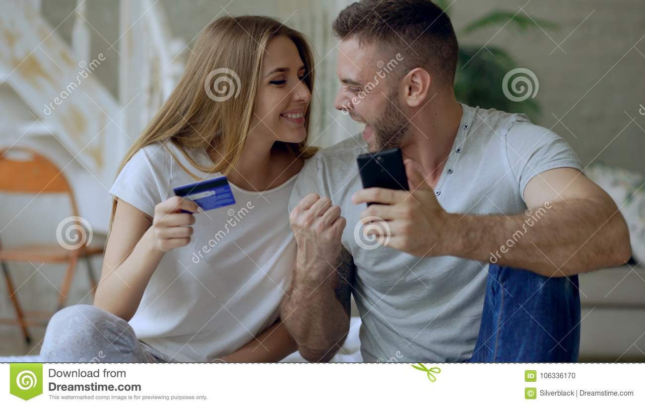 Attractive young couple with smartphone and credit card shopping on the internet sit on bed at home