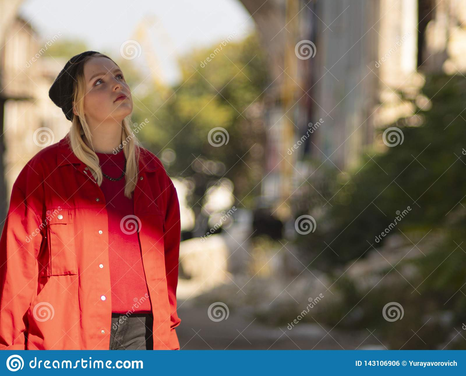 Attractive young female blonde teenager in a red jacket standing on the street