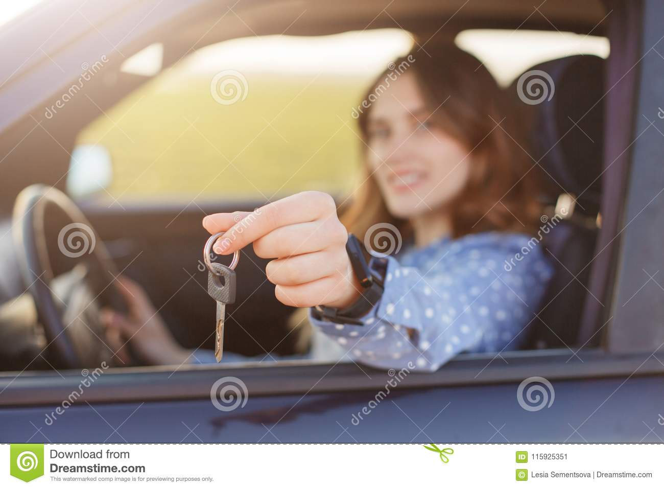 Attractive young female holds car keys, being happy owner of new automobile, blurred background. Lovely woman sells vehicle, adver