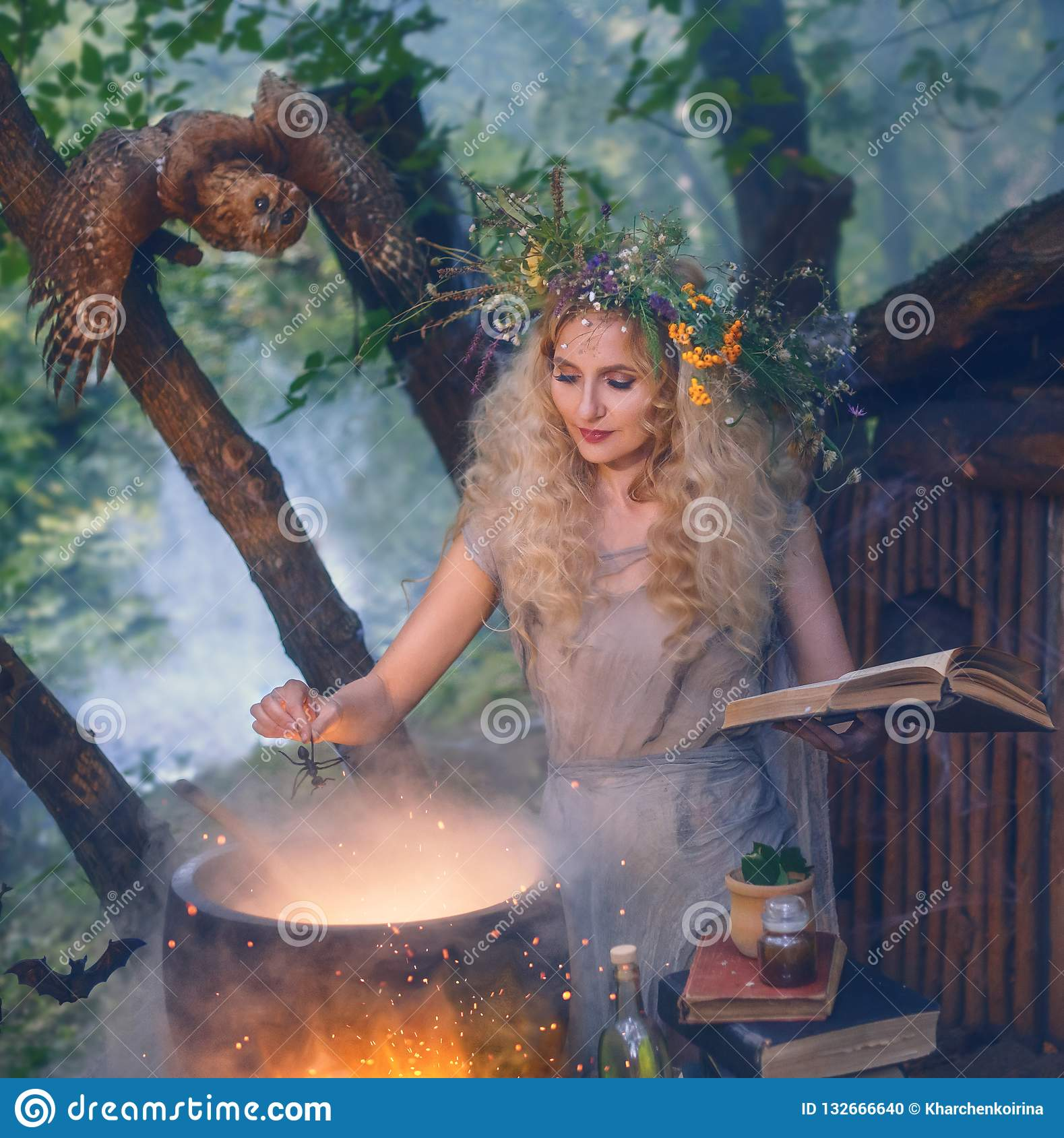 Attractive young girl with blond hair with an amazing lush wreath on her head in the forest, preparing potion in cauldro