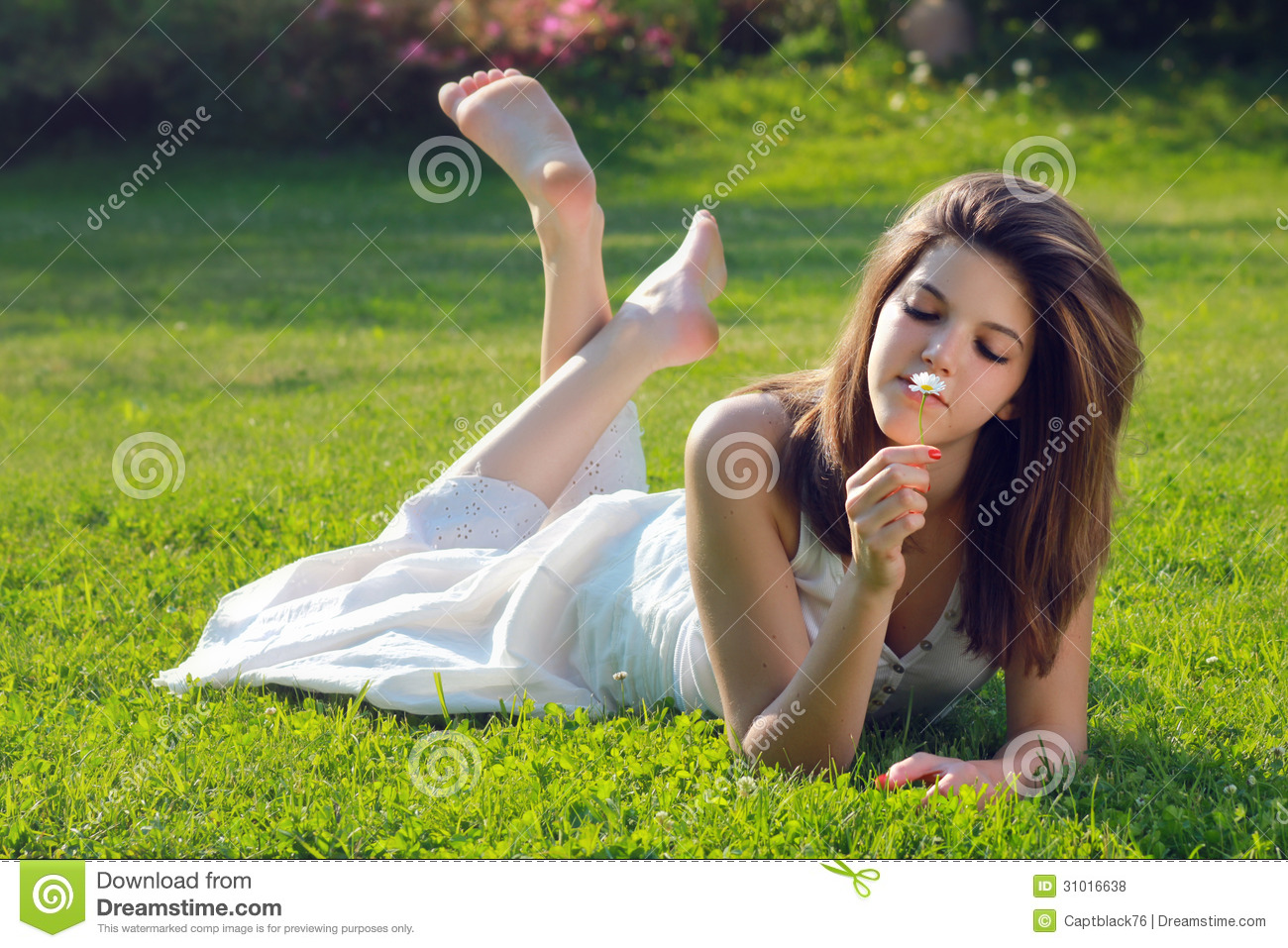 Attractive young girl with daisy lying on grass royalty for Pretty grass
