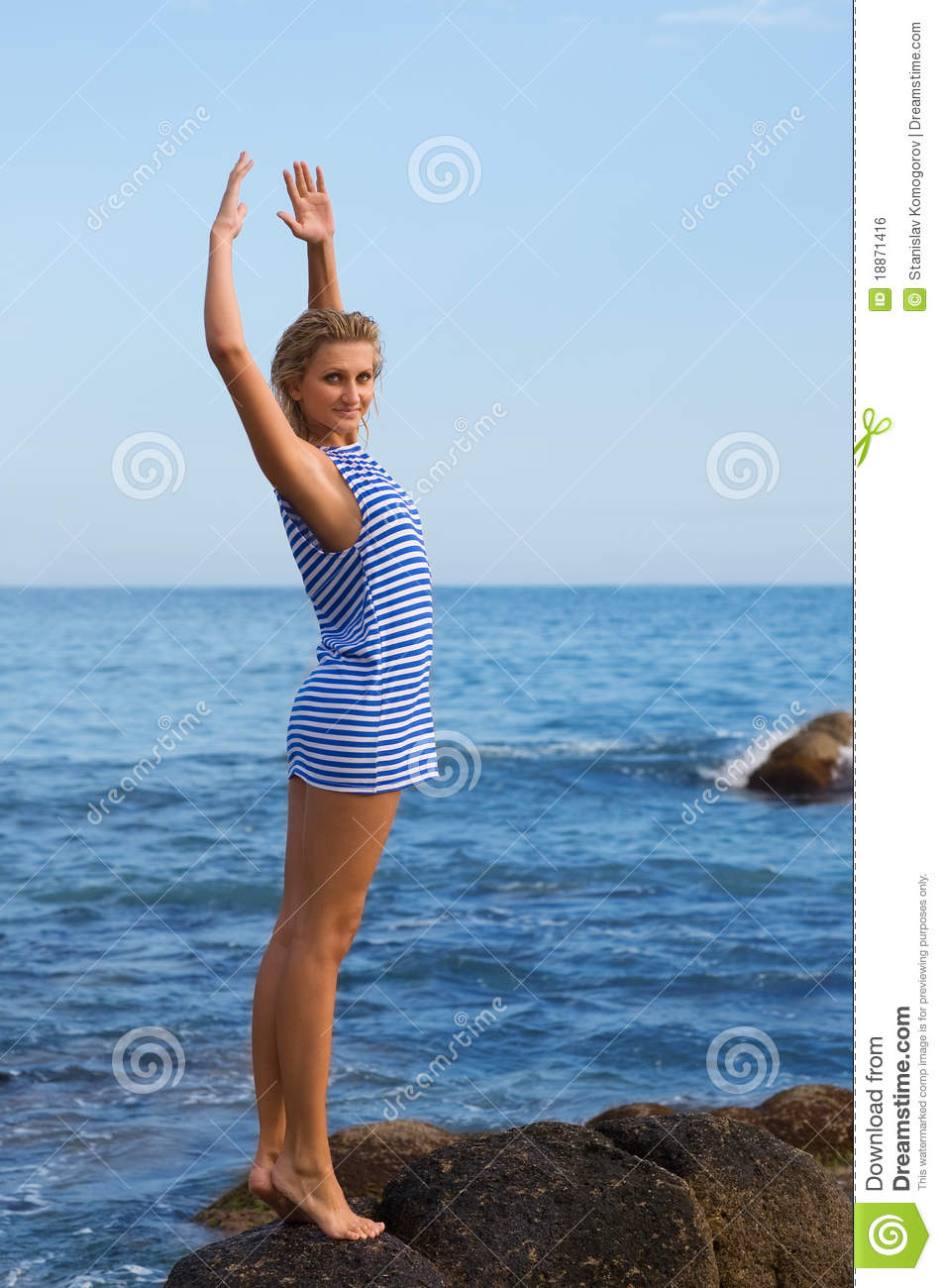 Attractive young girl on a rocky seashore.