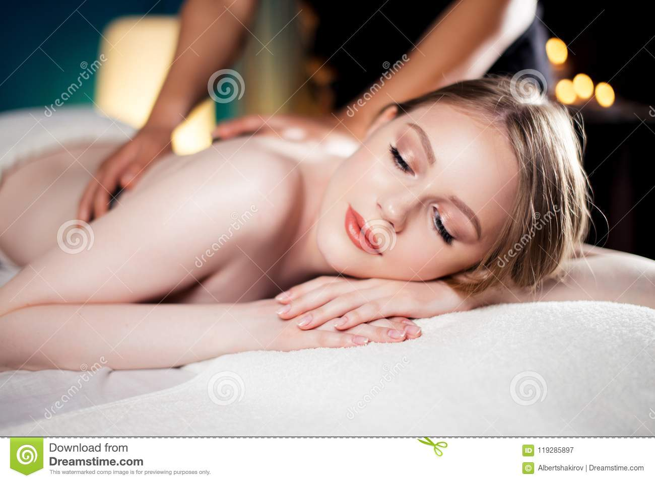 Attractive, young and healthy girl lying on massage bed in spa salon  receiving hot stone massage as pleasant bonus to the main Total Body  Oriental Massage.