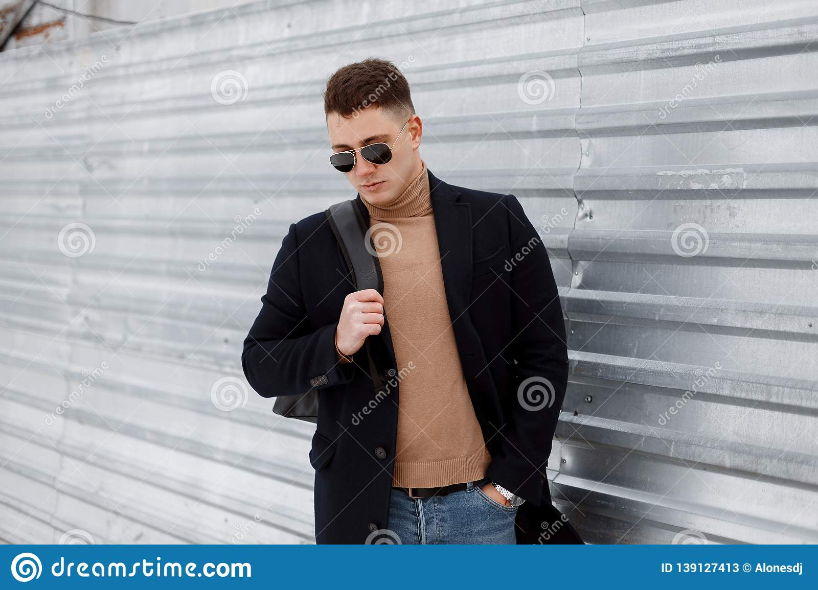 379ac70e9c2 Attractive young hipster man stylish sunglasses with a stylish hairstyle in  a vintage knitted sweater with