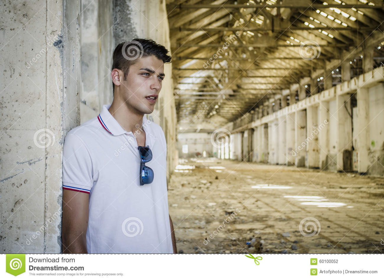 Attractive young man in abandoned, empty warehouse