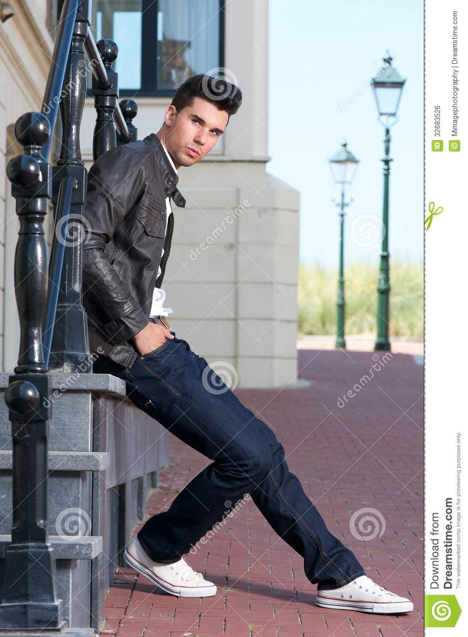 Attractive Young Man In Black Leather Jacket Sitting Outdoors ...