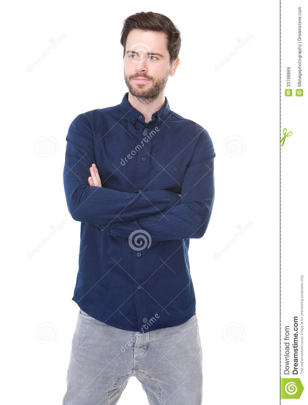Attractive young man standing with arms crossed and looking away