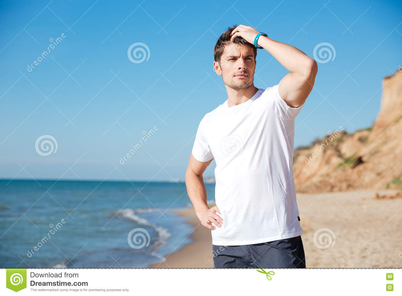 Closeup of attractive young man in white t-shirt standing and thinking on  the beach 6c37b22dc