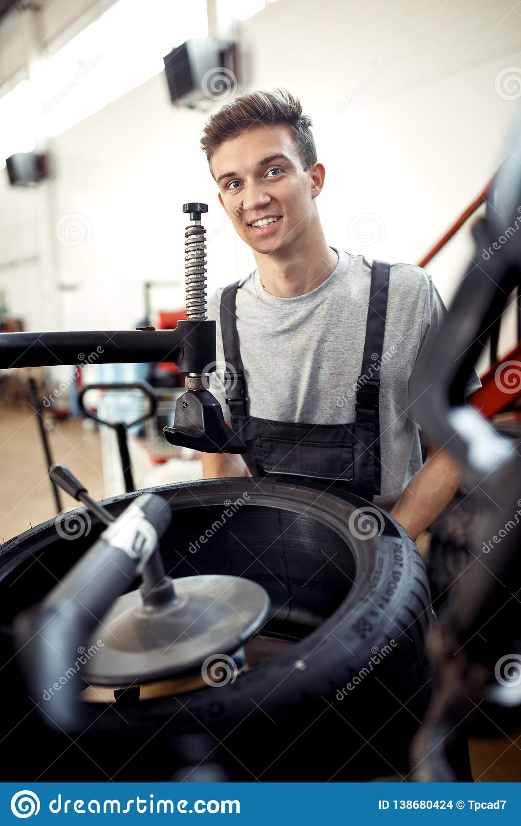 An attractive young mechanic is smiling while working at a car workshop