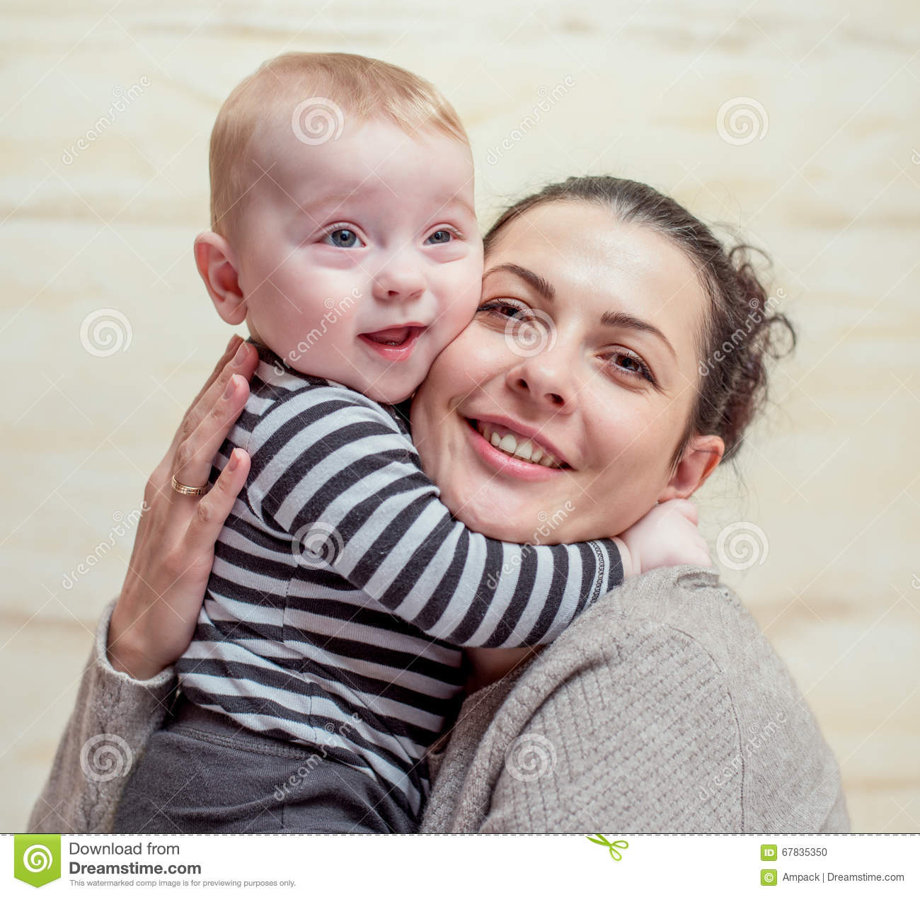 Attractive young mother hugging her little baby