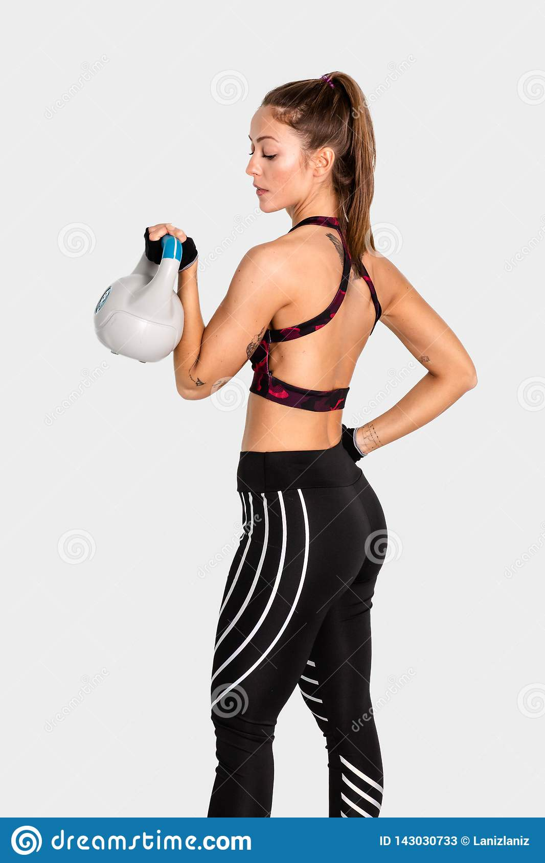 Attractive young with muscular body exercising crossfit. Woman in sportswear doing crossfit workout with kettle bell. Image