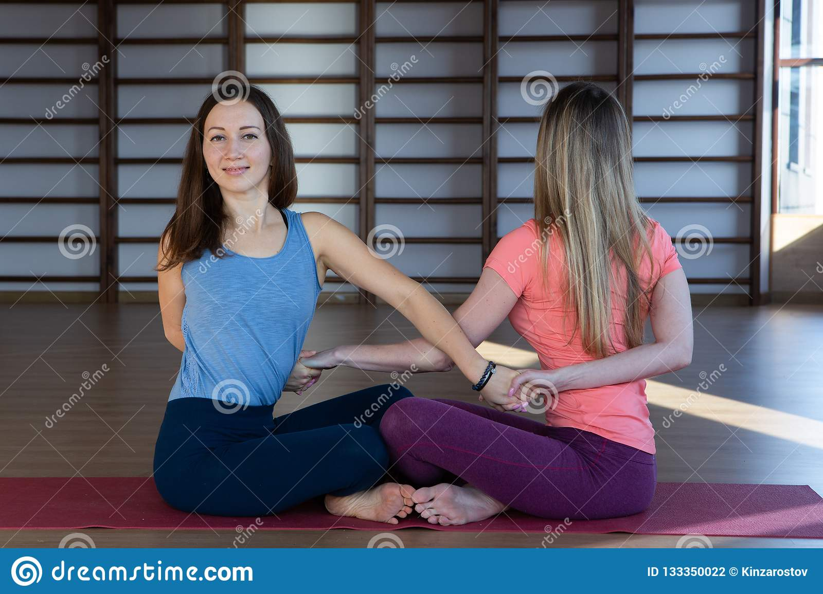 Attractive young sport girls are doing yoga together. Group training