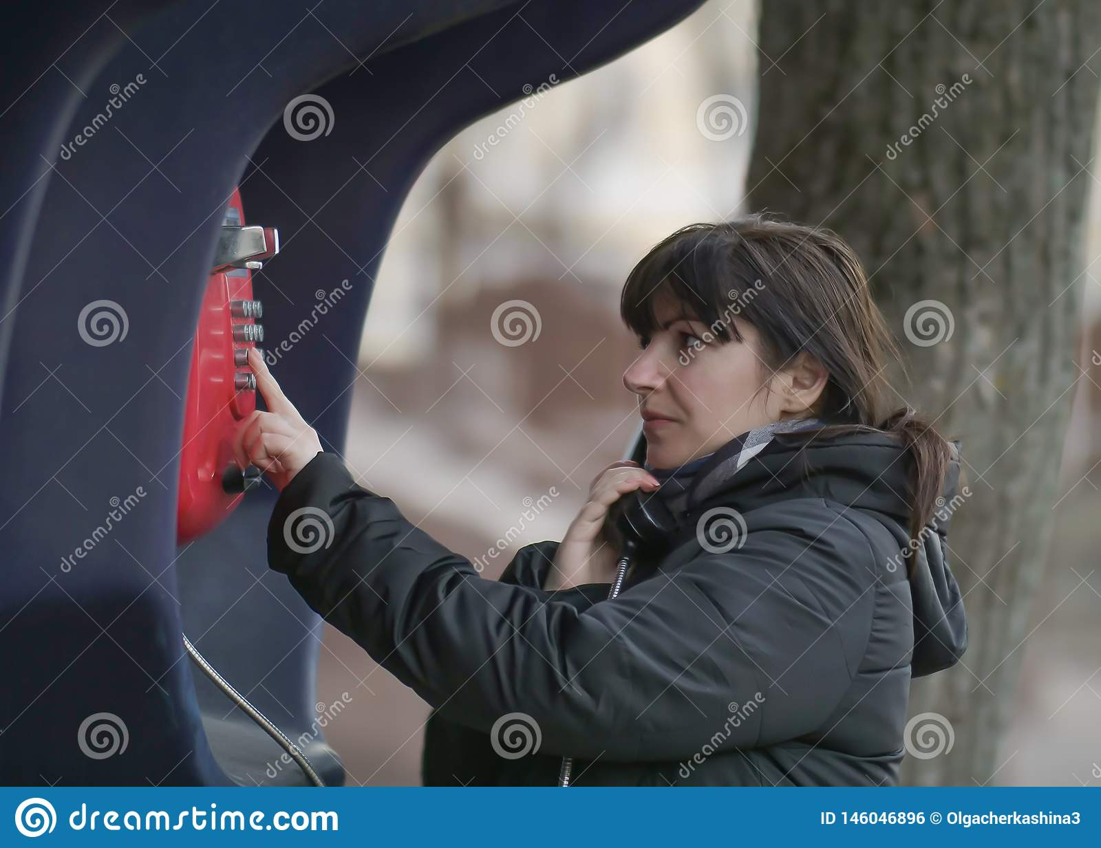 Attractive young woman calling from a red street payphone