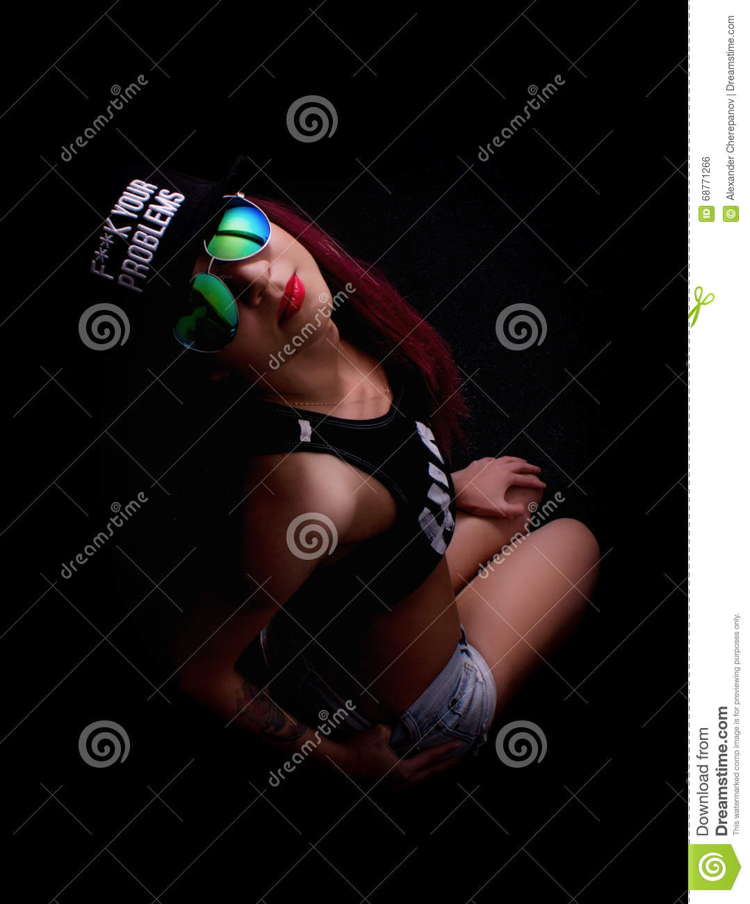 Attractive young woman in cap and sunglasses, smokes on a dark background. Be trendy, be rapper