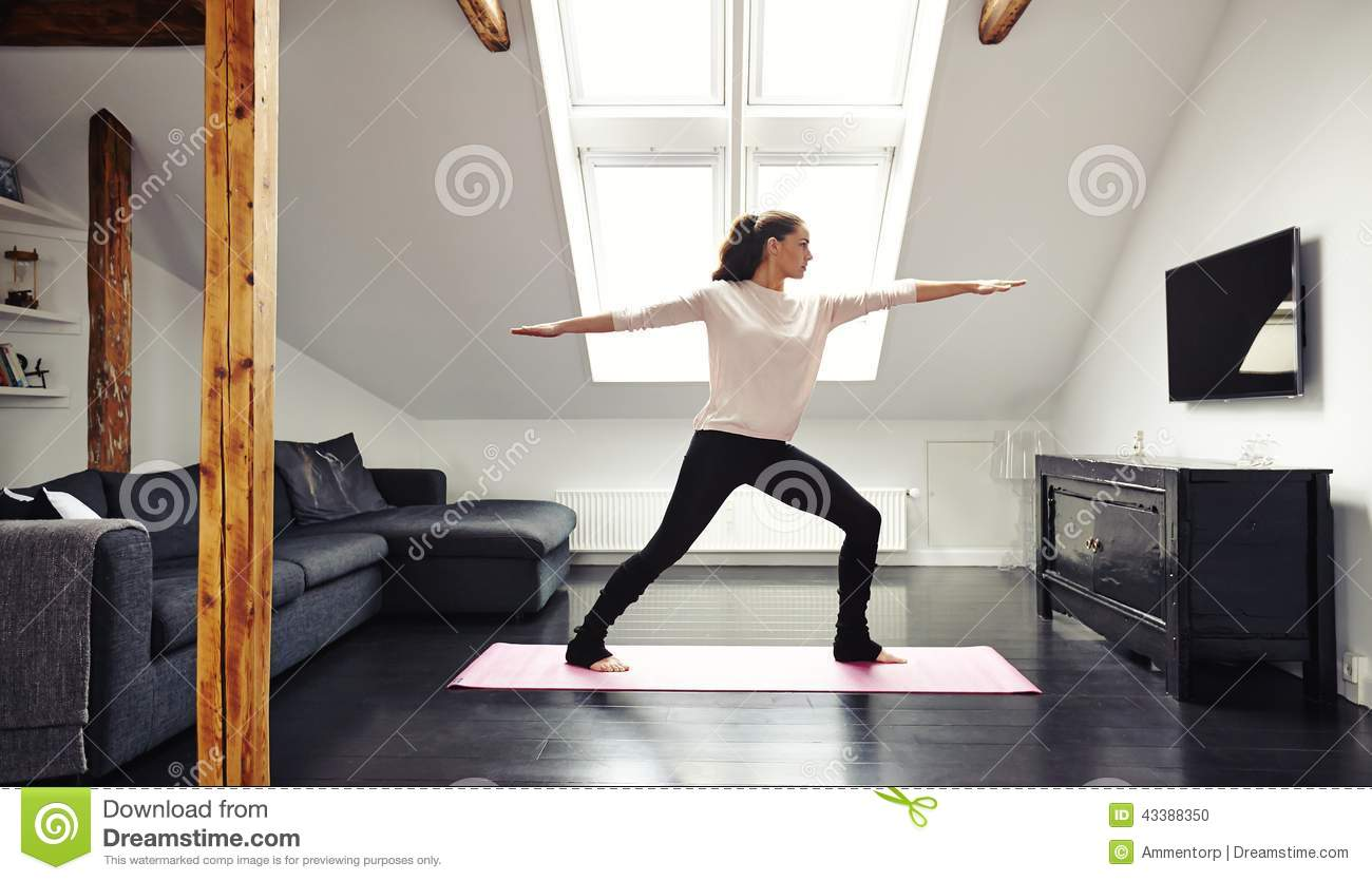 Attractive young woman doing yoga at home stock photo for Living room yoga timetable