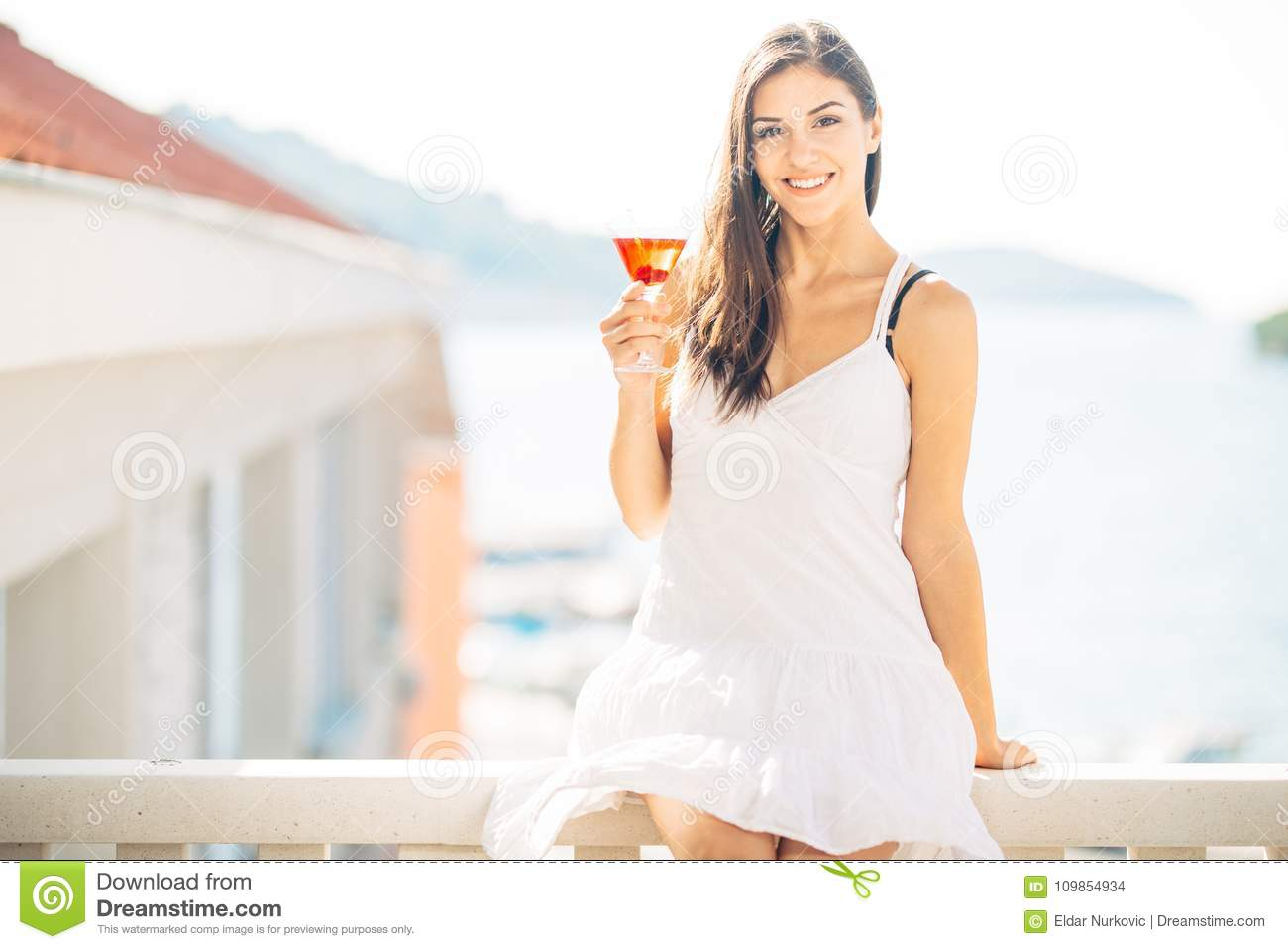 Attractive young woman drinking fruit alcoholic cocktail and enjoying her summer vacation.Holding glass of cold refreshing drink