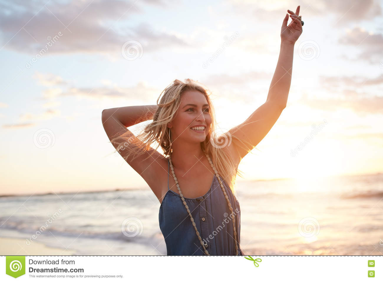 Attractive young woman enjoying on the beach at sunset