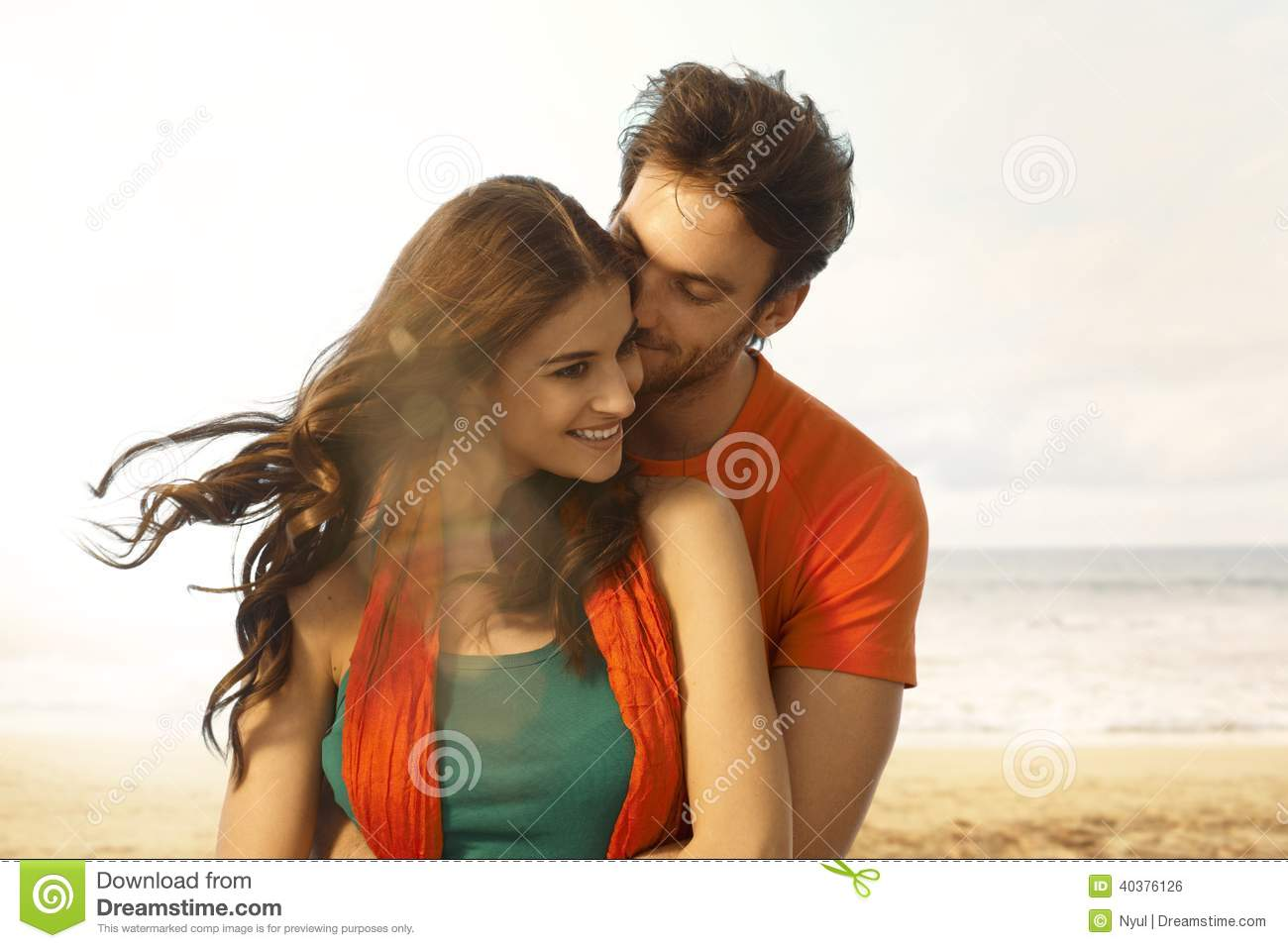 Attractive young woman getting a kiss at beach
