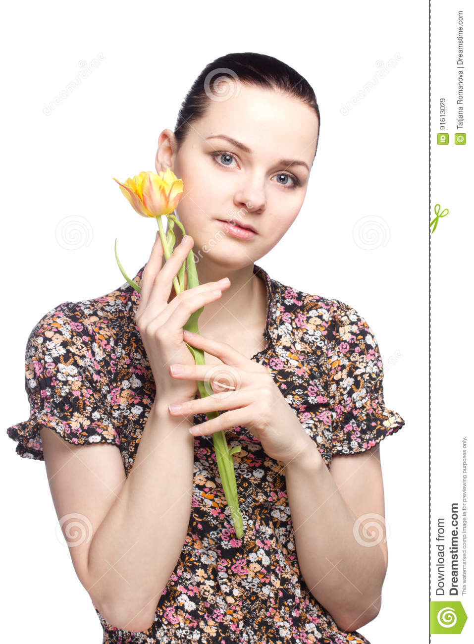 Attractive young woman holding a yellow tulip