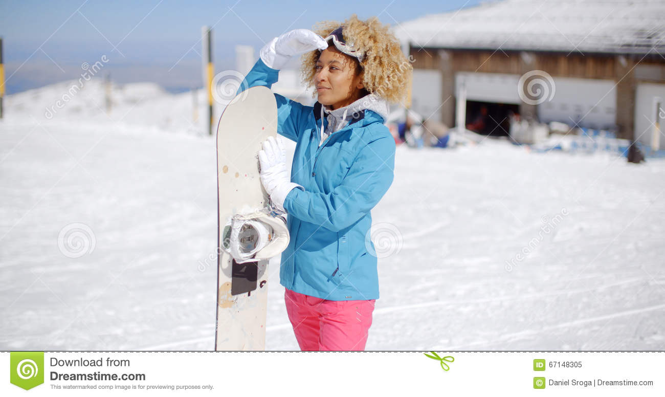 02d38fb581 Attractive young woman posing at a winter ski resort in her ski clothes  holding her snowboard and smiling at the camera with copy space