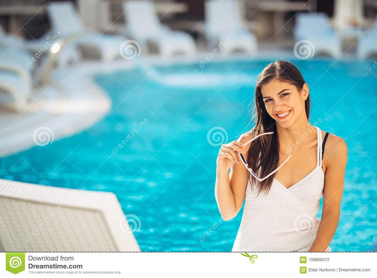 Attractive young woman relaxing at nluxury vacation resort pool.Enjoying summer.Vacation mood.Girl at travel spa resort pool.Flirt