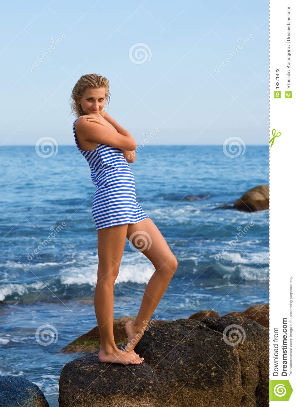 Attractive young woman on a rocky seashore.