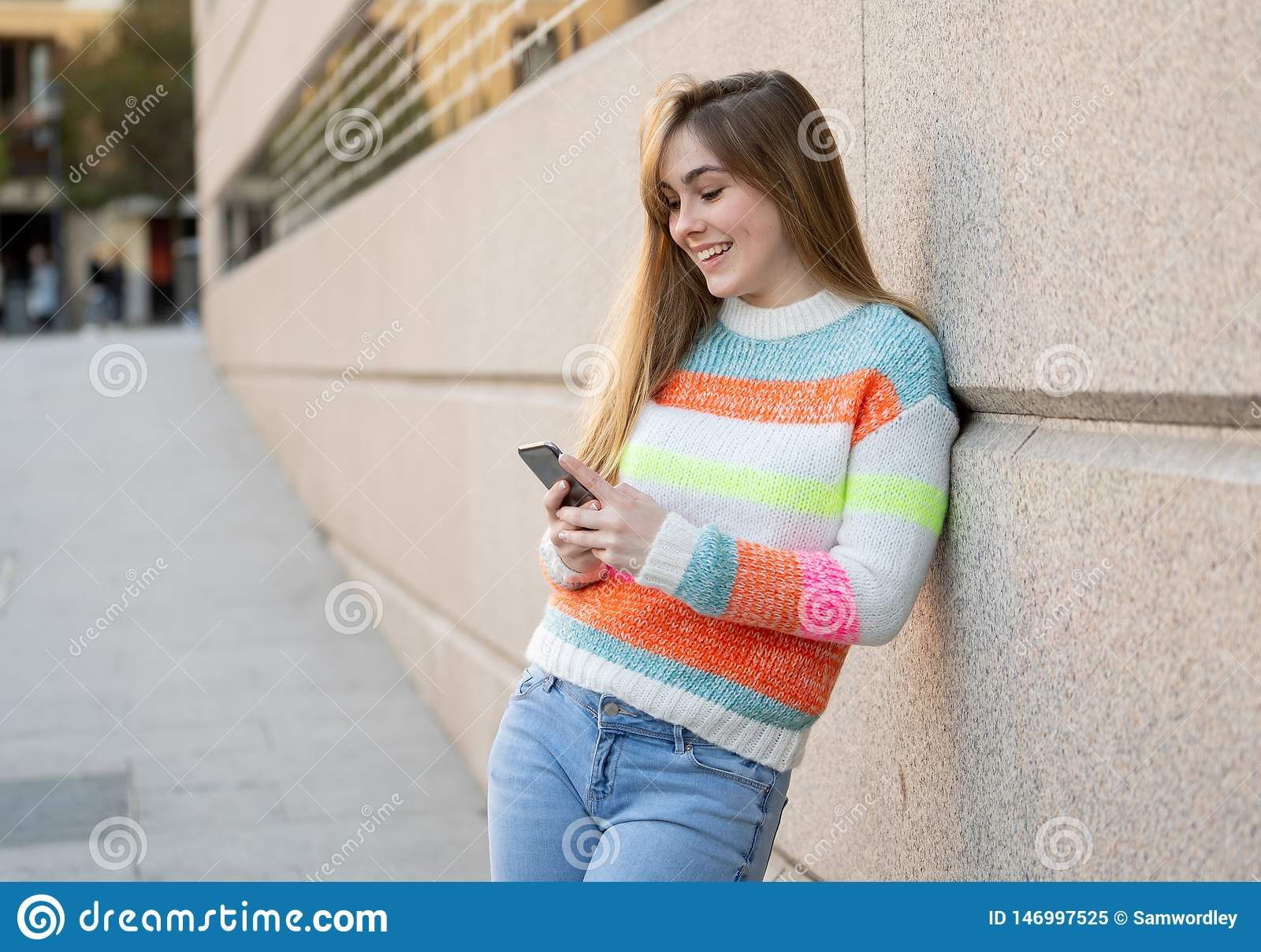 Attractive young woman on smart phone checking social media mobile apps outside city