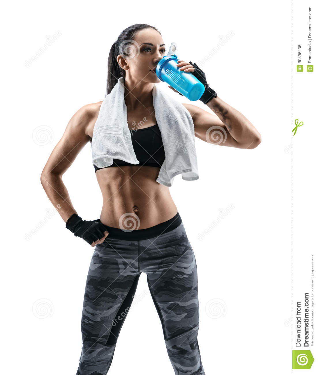 Attractive young woman in sports wear and with towel on shoulders drink protein cocktail in special shaker