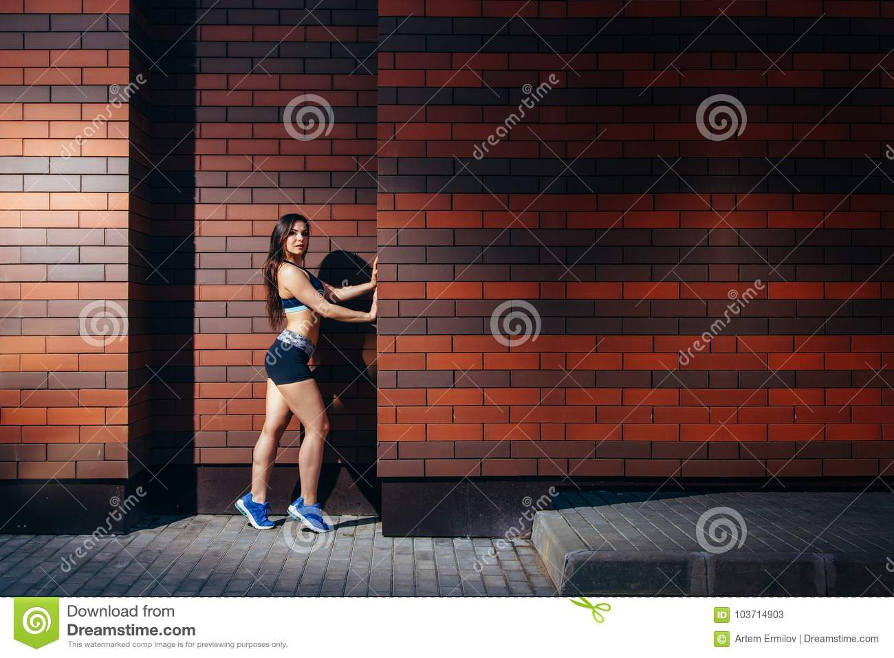 An attractive young woman in sportswear posing against a brick wall background with copyspace. Training outdoors