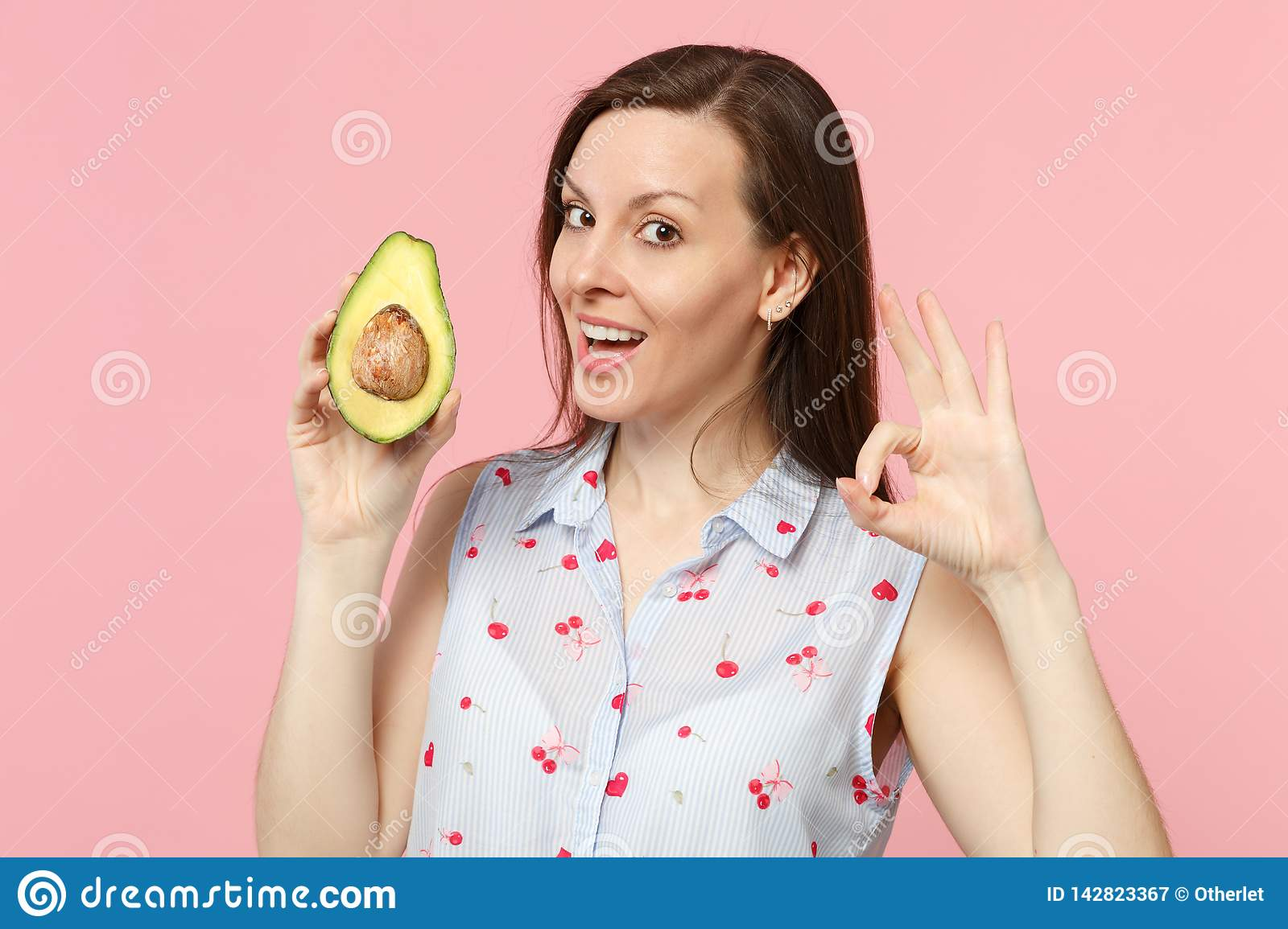 Attractive young woman in summer clothes showing OK gesture, hold fresh ripe green avocado fruit isolated on pink pastel