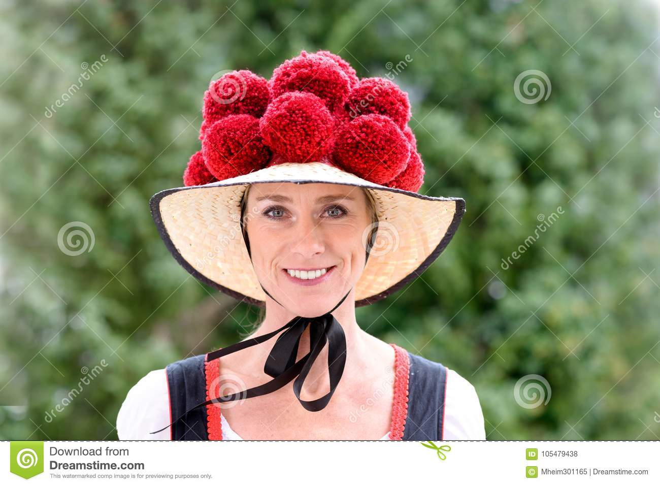 Attractive young woman wearing a traditional Black Forest Bollenhut with  its 14 pompoms as she smiles at the camera outdoors against greenery 137b601f48db