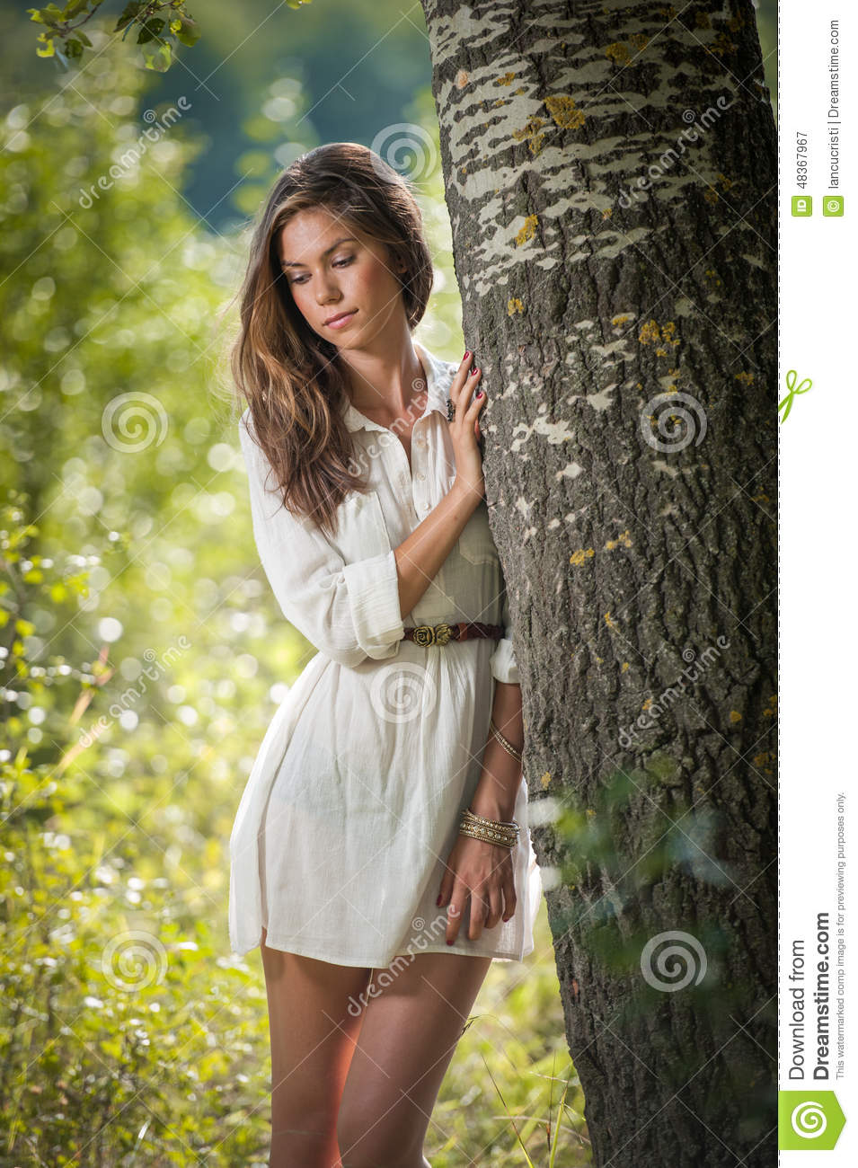 Attractive Young Woman In White Short Dress Posing Near A