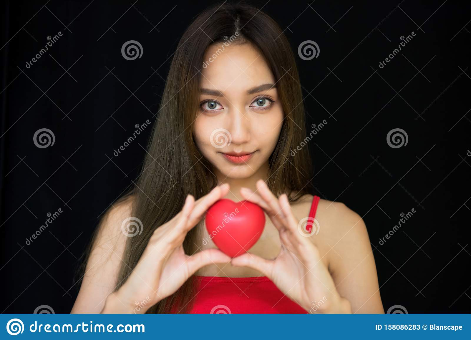 girl hold red heart toy