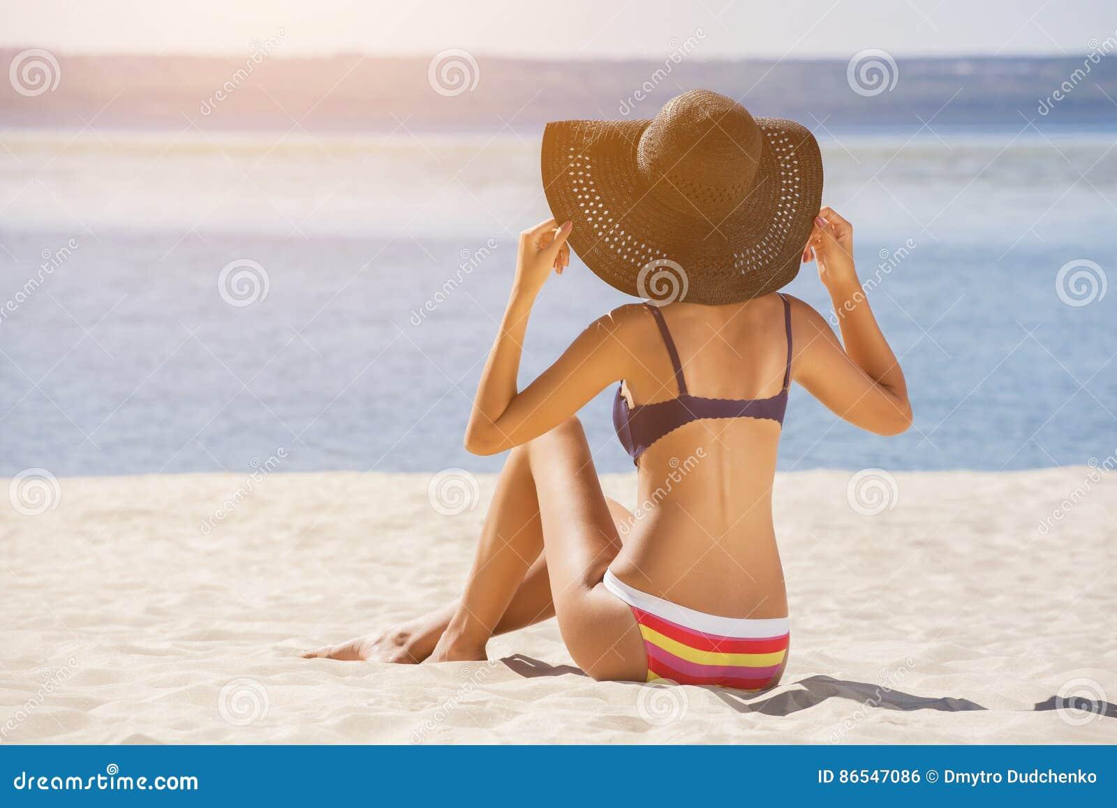 Attraente ragazza in un costume da bagno che si siede sulla spiaggia e che prende il sole sul - Bambolotti che fanno il bagno ...