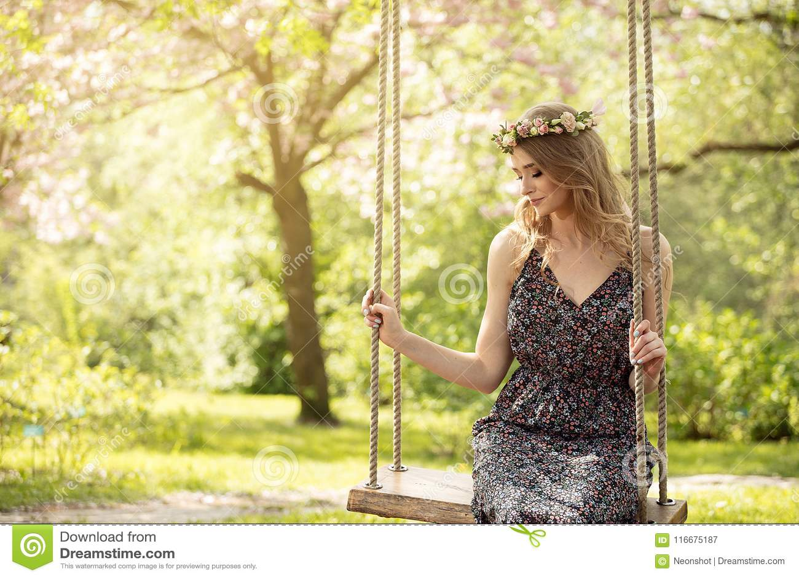 Attraktiv blond flicka i blommande trädgård