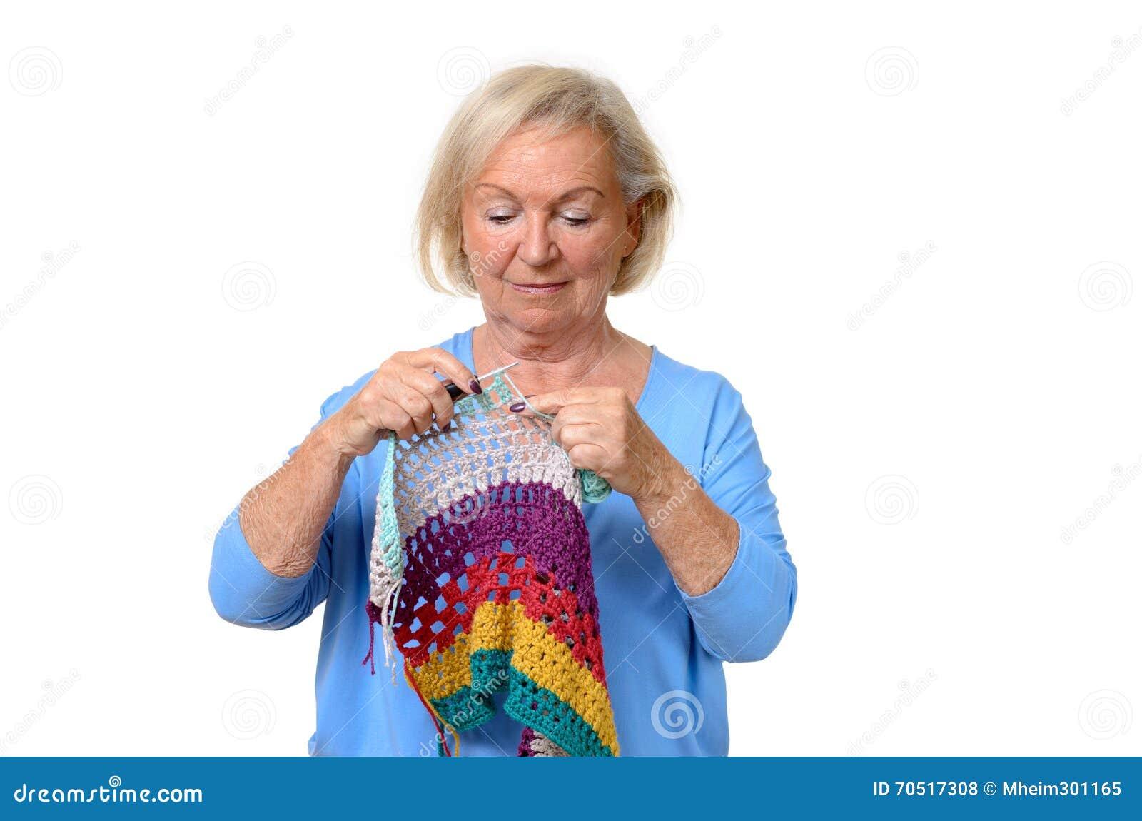Attraktiv blond hög dam som gör hennes handarbete