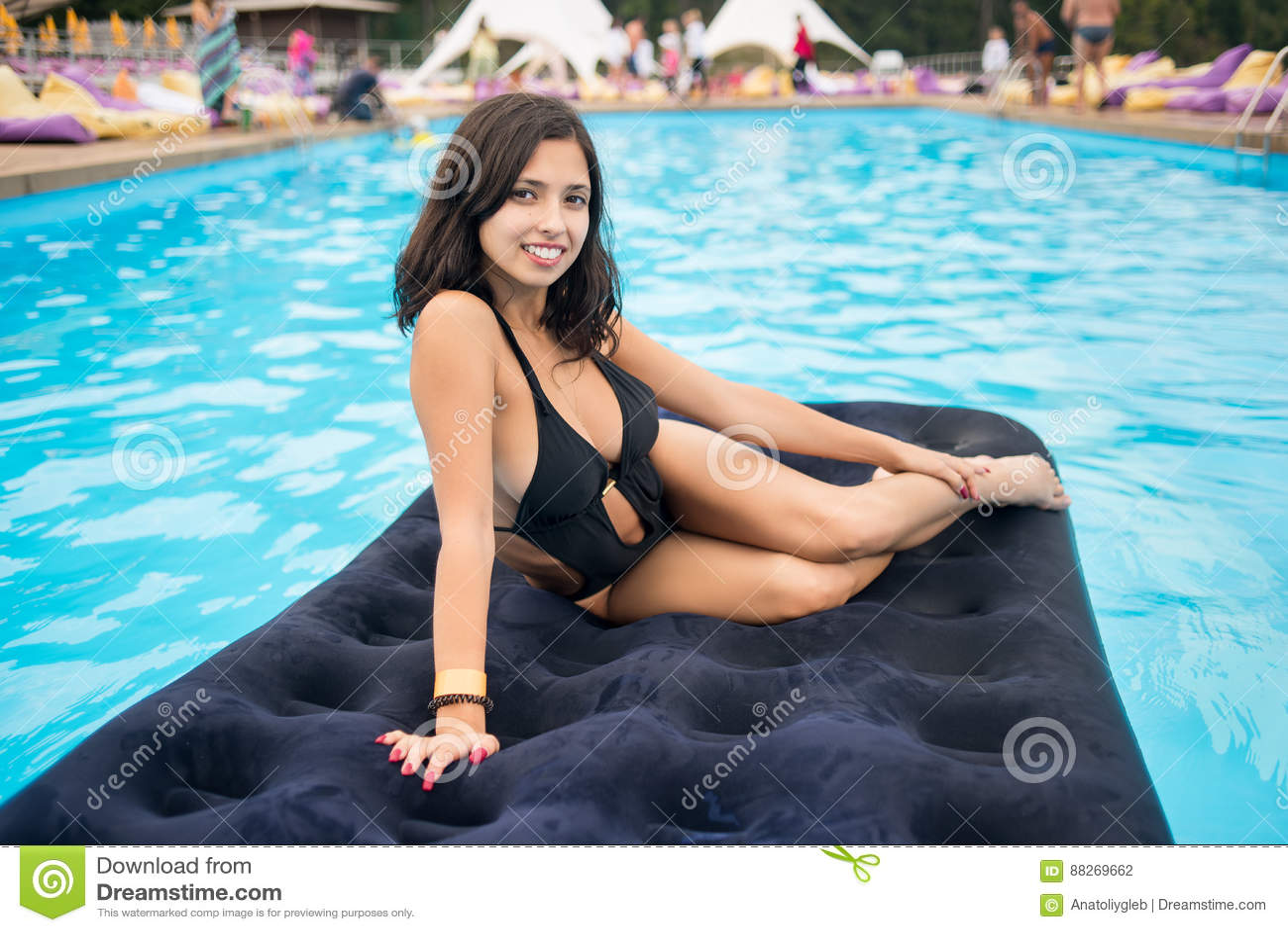 Attraktiv brunettflicka i den svarta bikinin som ligger på en uppblåsbar madrass i pöl med suddig bakgrund