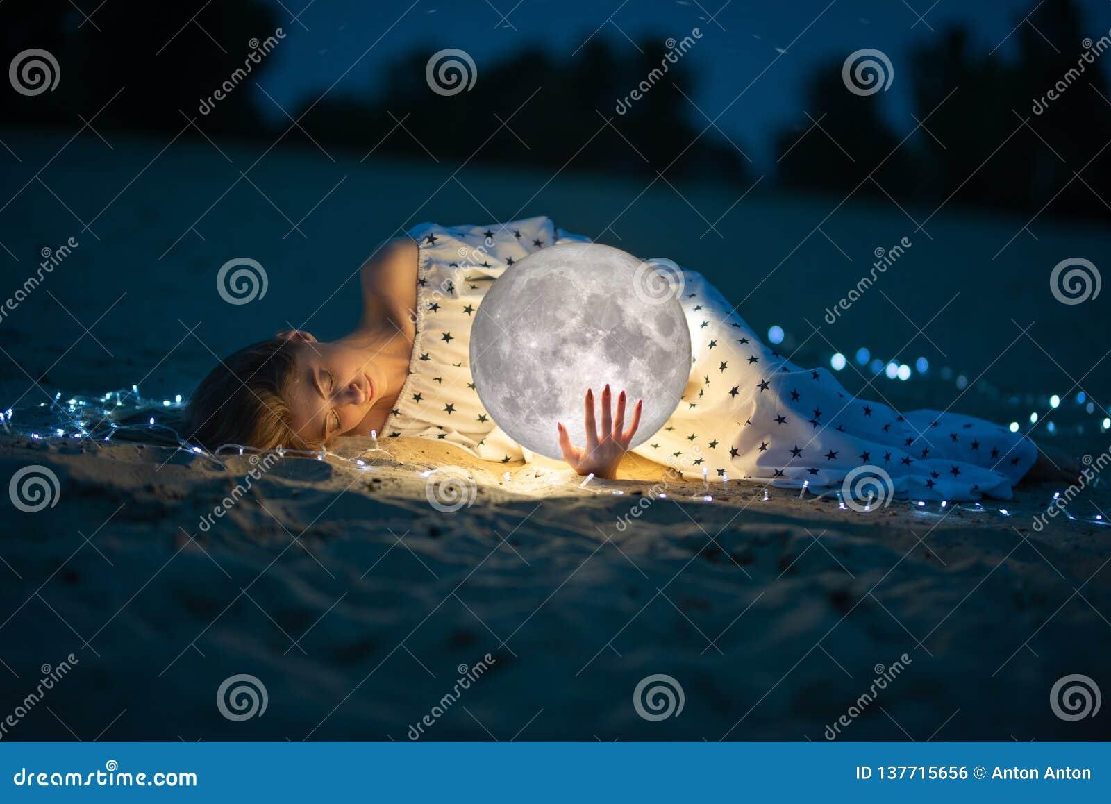 Attraktiv flicka på stranden och kramarna månen, med en stjärnklar himmel Konstnärligt foto